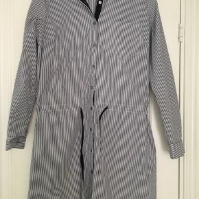 Smuk og klassisk skjorte-kjole fra Gestuz. Hvid med blå striber. Bånd der kan snøres ind i taljen.
