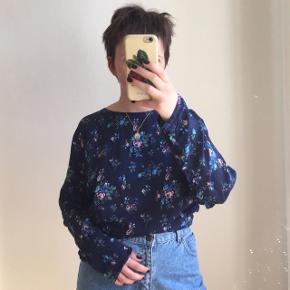 Blå blomstret bluse fra Mads Nørgaard. Den har en flæsen på ryggen og ærmerne. Den knappes i ryggen. Lavet af 100% viskose. Størrelse 42. Jeg er selv en størrelse S.