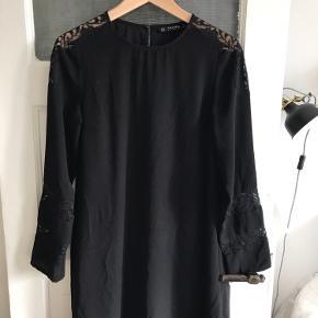 Virkelig fin sort kjole fra zara basic. Kjolen har blonder ved skuldrene og ærmerne. Derudover lukkes den med en knap i nakken. Kjolen fungere også rigtig godt med et bælte i taljen.