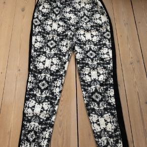 Mønstret bukser med knap foran og en lille slids foran ved anklen. Sort stribe ned langs hver bukseben i siden. Str. 38 Materiale: 90 % polyester, 10% bomuld.  Helt nye.