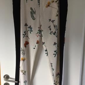 Custommade buks, by numbers 54/267. Blomstermønster på råhvid bund, sort sidestykke, lommekant og linning.  Bytter ikke.