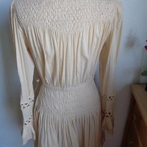 Sød og romantisk slåom kjole med fine detaljer i farven Nude. Der er elastiksmock foroven og på ærmerne. Der er hulmønster forneden og på ærmerne. En masse syede læg i livet. Lukkes inderst med en knap og så bindebånd uden på. Der er trykknapper på det lille stykke i v-udskæringen. Tror aldrig den er blevet brugt og ellers er det kun et par timer. Porto tillægges eller hent den på Amager