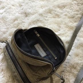 Fin taske, lynlås går lidt trægt og kan sætte sig fast. Farven er som det ses på billedet en mellemting mellem grå og brun. Jeg har ingen kvittering, da jeg selv har købt den på lommemarked. Kom med et bud, jeg er klar på en hurtig handel.