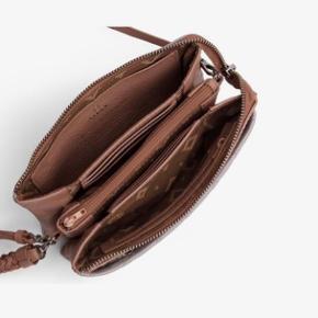 Adax Combi clutch Nellie Capri  Kalveskind. Aftagelig håndledsrem. Skulderremmen er justerbar og kan tages af.  Plads til seks kort og lynlås lomme til evt. mønter.  Der er to store rum samt to mindre. Mål / 20x12x3 Materiale / Skind  Ny pris 1099kr.  Sælges for 750kr