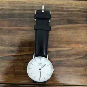 Daniel Wellington Classic Sheffield ur med sort læder og sølv urskive. Urskiven måler 36 mm.  Uret er brugt få gange og fremstår derfor i fin stand kun med brugstegn omkring læderet, hvor uret spændes. 😊 Nypris var 1.299 kr.