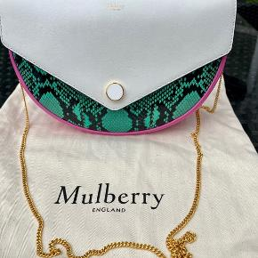 Mulberry, Brockwell Clutch, Viridian Green, Rasberry Pink & Midnight Silky Calf & Python. Clutch har en flot halvmåne form, med en flot lang guldkæde så man kan bruge den som en crossover.  Tasken er 25 cm bred for oven, samt 17 cm høj. Bunden som gør der kan være meget i tasken er 7 cm.  Lige under den lille lås nederst på tasken er bredden ca 16 cm.  For at give lidt bredden forneden i den måneformede taske. Kæden er 115 cm lang    Tasken er købt i Mulberry England på udsalg,hvor kvitteringen på kr 4.245,00 er fra.