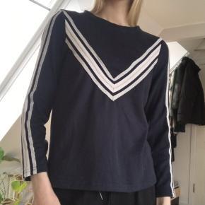 Mørkeblå bluse med grå mønster på front og ærmer.