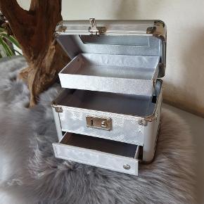 """Flot sølv beautybox  Lukkes/åbnes med en """"klik-lås""""  Lille spejl inden i låget  Der er stadig plastik omkring håndtaget på låget"""