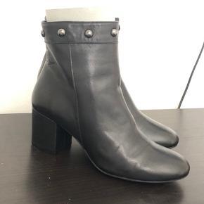 Sorte læderstøvler med hæl fra Angulus. Støvlen er behagelig at gå i, har lynlås på indersiden og har en flot afslutningskant smed blanke nitter.  Ubrugte.  Jeg sender gerne.