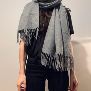 Modström gråt strik halstørklæde i 100% uld. Måler 190cm langt og 72cm bredt. Aldrig brugt.
