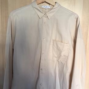 Skjorte i bomuld, nylon og spandex, så den har en form for strækkvalitet over sig. Har ingen tydelige mærker på brug.