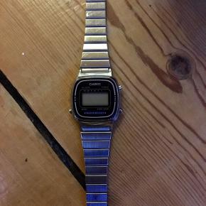 Klassisk retro ur fra Casio med stålrem og sort skive  Model nr.: LA670WE  Original købsemballage følger med, og købsbevis kan også fremvises  Uret er brugt, og har et par ridser. Batteriet virker ikke længere, og skal derfor skiftes