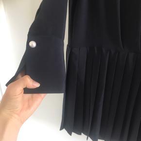 Smuk skjortekjole hvor underdelen er plisseret. Farven er meget mørkeblå, så ret tæt på sort. Perleknapper ved hals og håndled, og knapper ned til under brystet, så dermed ammevenlig. Sidder løst, så man kan sagtens spise en ekstra portion eller skjule en babybule :-) Kan også gå til vinter med fine tights under.