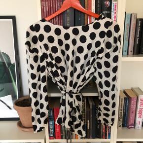 Fin sort og hvid prikket bluse der bindes på ryggen. Har selv købt den brugt, men aldrig selv brugt den☺️