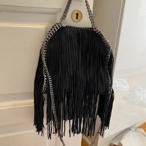 Stella McCartney special edition taske i sort med frynser.  • Brugt få gange  • Dustbag medfølger • Købt hos Filuca V • Fragt er med i prisen
