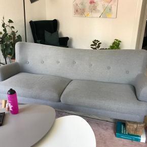 Grå sofa, hvor det ene ben er faldet af, men kan sættes på igen med en ny skrue. Cirka L.3m, B.90cm og h.120cm.