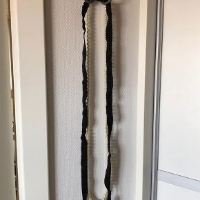 Perlekæde påsat sort bånd. Længde kæde: 110cm.