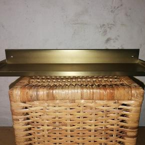 Hylde i messing. Aldrig brugt, dog med nogle helt små, tynde ridser i metallet (ikke noget, der betyder noget, når hylden er i brug).  Længde: ca. 30-35 cm.