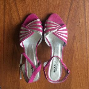 Åbne stiletter / sandaler i pink ruskind og sølv med justerbare stropper om anklerne.  Aldrig brugt (fejlkøb) - kun prøvet indendørs.  Kan bruges af str. 38 og 39.  Nypris: 499 kr.