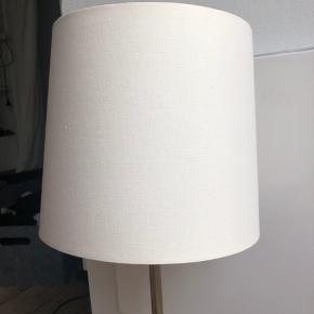 """Fin retro lampe i guld med hvid/beige skærm.  Lampen er cirka 64cm høj, og skærmen måler en omkreds på cirka 67cm på længste sted og cirka 62cm på det korteste sted.  Kan bruges både som bordlampe eller en mindre gulvlampe. Lampen er i rigtig fin stand, men den """"flimrer"""" når den tændes, så pæren skal nok skiftes.   BYD!  Lampen kan sendes mod betaling eller afhentes i Gentofte/Kbh."""