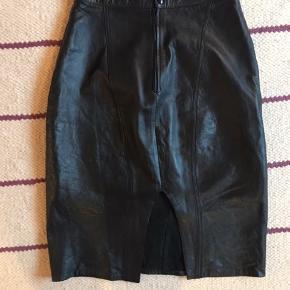 Vintage lædernederdel (nederdel i skind) med slid og lukning med lynlås og knap bagtil. Knælængde