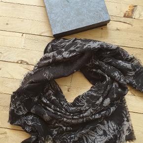 Det har kostet 800,- og er af ren blød uld. Det måler 140 x 140 Farve: sort / grå