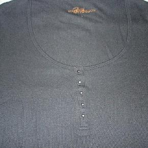 """Varetype: Smuk bluse i sort med meget flot udskæring og knapliste Farve: Sort  Super lækker sort bluse med lange ærmer med lille slids og smuk halsudskæring med yndig knapliste med kugleformede metal-""""knapper"""" i størrelse XL. Blusen runder flot forneden. Blusen måler over brystet 98 cm. Længden er 65 cm. Brugt en enkelt gang og fremstår i flot stand. BYTTER IKKE!"""