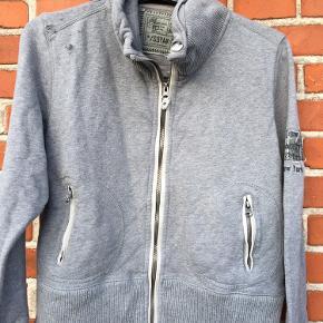 Lækker grå trøje med lynlås. Lidt kraftig kvalitet.  Desværre har vires kanin været for tæt på, se små huller på højre skulder. Ellers fin.