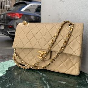 Ældre Chanel Flap bag i beige.  Tasken fremstår i flot velholdt stand, med små naturlige brugsspor.  Der medfølger ikke originalt købstilbehør til tasken.  Tasken måler ca 22x16cm.