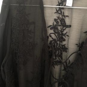 Sort kjole i transparent (dog ekstra stof fra talje og ned) med blonde broderi. Nedringet med snøre.