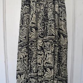 Nederdelen er oprindeligt købt i en vintagebutik, men jeg har aldrig selv brugt den, så den er i god stand.  Der er elastik bagpå og lynlås i siden.  Kvalitet: 100% viskose  Længde: 92 cm.   Kan afhentes i Aarhus C eller modtages med post.