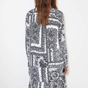 Lækker skjorte/style Cologne fra By Malene Birger i hvis med sort mønster. Skjorten er lang og har et løstsiddende fit. Lukkes med 7 hvide knapper, med en lille guld detalje i hver knap, samt 2 hvide knapper for enden af hvert ærme.  En skræddersyet men stadig løs skjorte passer til enhver lejlighed, og du vil vælge denne igen og igen. Denne flotte skjorte er en nyfortolkning af en gammel klassiker i garderoben med en sænket afrundet søm og en kort krave. Mønstret er inspireret af vintage blonder, men de er placeret på en måde, der passer til et mere moderne look. Almindelig pasform Afrundet søm To knapper ved ærmekanterne 66% viskose, 34% silke Håndvask maskinvask I butikkerne nu. 1000 kr - bytter ikke  Nedsat til 800pp  Og nu 750 incl