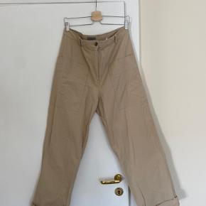 Sælger disse fede bukser fra COS i en str. 42. Har tegn på brug, og derfor sælges de også billigt. Nypris var 600 kr. Folden forneden kan også foldes ud.