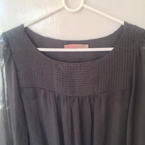 Koksgrå løstsiddende top/bluse med let gennemsigtige ærmer.  Elastikkanter ved ærmer og forneden, så den kan 'puffes' op.  Er kun brugt få gange, da den desværre er for stor til mig.