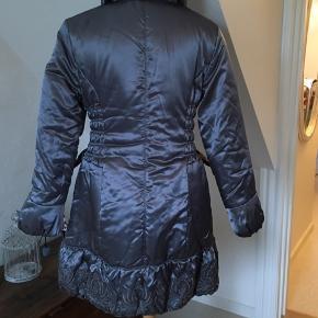"""Mega varm frakke i Polyester med """"dyne""""-foer - vaskes ved 30 g.  Fineste broderi forneden.  Lynlås og knapper foran.  Figursyet og med en brystvidde omkring 100 cm."""