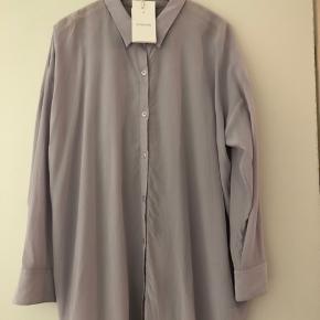Aldrig brugt lækker silkeskjorte model Bianca. Skøn lyslilla farve.   Str L men afhængig af hvordan man ønsker modellen kan den fint bruges af S og M.  Aldrig brugt.