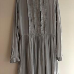 Meget fin og detaljerig kjole. 100% polyester. Fin og glat.