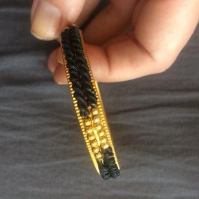 Flot vintage armbånd med detaljer af perler og en sort metalsnor.