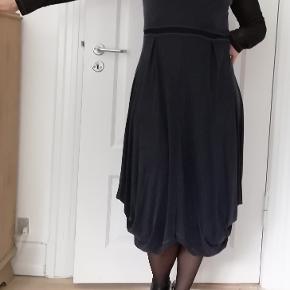 Bytter ikke. Eksklusiv porto. Utrolig lækker kjole, fra Beate Heymann, str. 40.  Kjolen stof falder flot. Kjolens ærmer er gennemsigtige, se billederne. Kjolen har lykra i stoffet, elastisk. Størrelsesguide str. 40: Bryst mål 92 cm   Talje mål 78 - 80 cm Hofte mål 98 - 102 cm 95% Cupro, 5% lykra, jersey Bryst vidde 96 cm (eller mere, da stoffet er elastiskt). Længde fra skulder og ned 116 cm Farve: Dark marine blå. Modellen på billederne er str. 38. 167 cm høj. Blot til information. Kommer fra et ikke ryger og parfume frit hjem. Hænger i dragtpose.