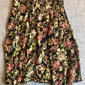 Ingen skader, men brugt.   Med lommer i siden og elastik bånd i taljen.   Sort med blomster.