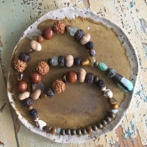Smuk rustik håndlavet halskæde :) Med keramisk håndlavet vedhæng af engelsk keramiker og perler fra rundt omkring i verden :) - lava sten  - tigerøje sten  - Howlit sten  - genbrugs glas - frø - vintage græskar kapsler - bronze   54 cm i omkreds - med elastik - uden lås, så skal trækkes over hovedet  Boho boheme  Hippie Earthy
