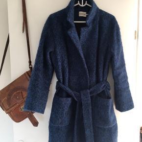 Smuk klassisk slå om-frakke i strukturmønstret bouclé-uld med bælte og store, påsyede lommer. Aldrig brugt, lækker uld frakke. Lad den stå åben eller understreg din figur ved at binde den i taljen. Kan afhentes i Skanderborg, sendes på modtagers regning. Passer også str small eller en large, der ønsker en lidt mere figurformet frakke.