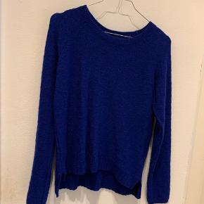 Fin, blå sweater med mønster, som har lidt fnuller. Officielt str. M, men fitter en S.