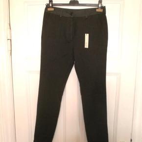 Nye bukser fra M. Grifone i 100% uld med detaljer i 100% bomuld. En størrelse italiensk 38, hvilket svarer til en dansk 34 XS. Men tjek taljemål for en sikkerheds skyld. Taljemål: 38 cm på tværs, dvs 76 cm i omkreds.  Aldrig brugt og stadig med tags.  Varetype: Nye koksgrå grå uldbukser uld bukser smalle klassiske Størrelse: It 38 Dk34 XS Farve: Koksgrå og army