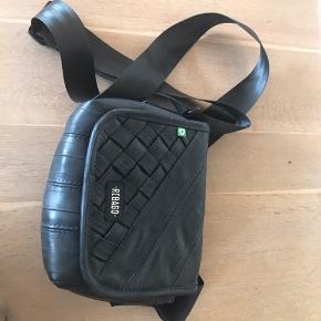 Taske fra Rebago lavet af cykelslange. Tasken har en lomme med lynlås og en til mobilen. Tasken lukkes med velcro.  Tasken måler:  Bredde: 22 cm Højde: 16 cm Dybde: 10 cm