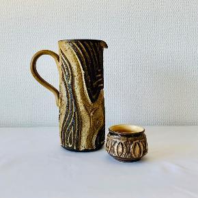Smuk og unik kande og skål fra Løvemose keramik. Løvemose Keramik i Kædeby på Langeland, blev grundlagt af pottemager Johannes Hansen og hustruen Marie Hansen i 1942. Som de drev sammen indtil 1982, en overgang med 15 ansatte. Løvemose blev blandt andet solgt til mange udflugtsgæster og turister, og derfor findes meget af keramikken i dag i udlandet. Mål kande: Højde: 23,7 cm Diameter: 10 cm Mål skål: Højde: 6 cm Diameter: 7 cm