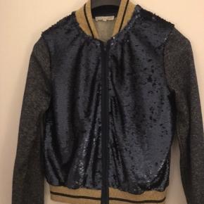 Super fed jakke fra mærket Millinium. Palliet på frontstykket, glimmerærmer og bagstykke. Blå med guldglimmer. Nypris: 599 kr