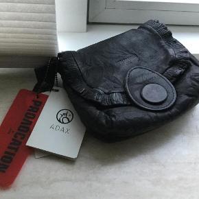 Brand: Adax Provocation Varetype: Clutch/Taske Størrelse: 17 x 15 cm Farve: Mørkegrå  Flot Clutch/Taske med søde detaljer.Aldrig brugt.Farven er mørkegrå,næsten sort. Tasken er lavet af ægte læder,garvet efter en unik metode specielt udviklet til denne taskeserie. Variationer i farve og læderets overflade er en del af taskens særlige karakter.