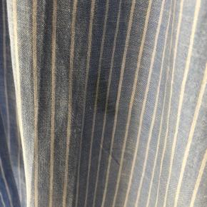 Fin, stribet skjortekjole i hørkvalitet med bindebånd (kan også bruges uden). Der er en lille plet/misfarvning (se billede 2, har ikke forsøgt at fjerne den, prisen sat derefter). Ellers fin stand.