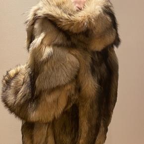 Fantastisk lækker ægte ulve pels i moderne snit med hætte og store ærmer . Det er str 38 men det er en oversize model - lukkes med hægter - flot stand